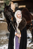 Портрет молодой белокурой женщины в черном плаще с лошадью Стоковые Фотографии RF
