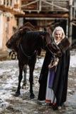 Портрет молодой белокурой женщины в черном плаще с лошадью Стоковое Изображение