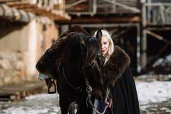 Портрет молодой белокурой женщины в черном плаще с лошадью Стоковые Изображения RF