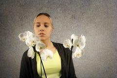 Портрет молодой белокурой усмехаясь женщины в вскользь одежде держа орхидею около ее стороны Стоковые Изображения