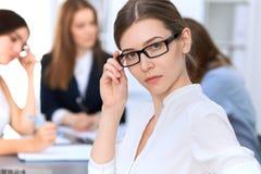 Портрет молодой бизнес-леди против группы в составе бизнесмены на встрече Стоковая Фотография RF