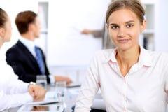Портрет молодой бизнес-леди против группы в составе бизнесмены на встрече Стоковое Изображение