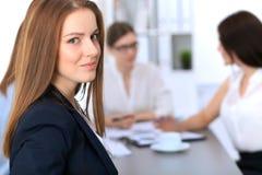 Портрет молодой бизнес-леди против группы в составе бизнесмены на встрече Стоковая Фотография