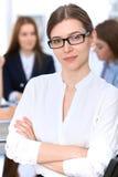Портрет молодой бизнес-леди против группы в составе бизнесмены на встрече Стоковое фото RF