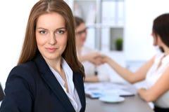 Портрет молодой бизнес-леди против группы в составе бизнесмены на встрече Стоковое Фото