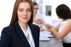 Портрет молодой бизнес-леди против группы в составе бизнесмены на встрече Стоковые Фото