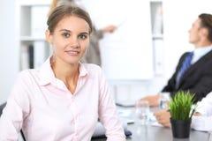 Портрет молодой бизнес-леди против группы в составе бизнесмены на встрече Стоковое Изображение RF