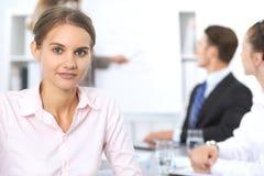 Портрет молодой бизнес-леди против группы в составе бизнесмены на встрече Стоковые Изображения RF