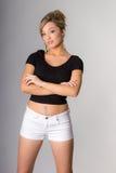Портрет молодой блондинкы, оружий сложенных, на серой предпосылке Стоковая Фотография RF