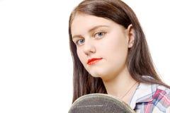 Портрет молодой девушки конькобежца держа скейтборд, изолированный дальше Стоковое Фото