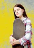 Портрет молодой девушки конькобежца держа скейтборд Стоковые Изображения