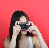 Портрет молодой женской держа винтажной камеры против задней части красного цвета Стоковые Фото