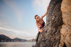 Портрет молодой женской скалы альпиниста утеса свисая Красивое голубое небо, горы города на предпосылке Стоковая Фотография RF