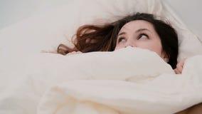 Портрет молодой женщины брюнет в кровати Красивая девушка пряча под листом, усмехаясь на камере Стоковые Фотографии RF