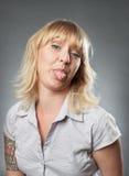 Портрет молодой женщины, вставляя вне ее язык Стоковая Фотография