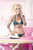 Портрет молодой женщины в бикини говоря на мобильном телефоне пока утюжащ Стоковое Фото