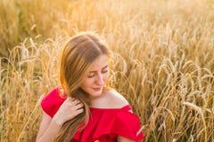 Портрет молодой женщины в красном платье на предпосылке золотых овсов field, лето outdoors Стоковое фото RF