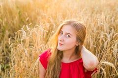 Портрет молодой женщины в красном платье на предпосылке золотых овсов field, лето outdoors Стоковое Фото