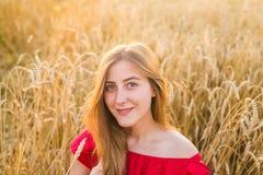 Портрет молодой женщины в красном платье на предпосылке золотых овсов field, лето outdoors Стоковое Изображение