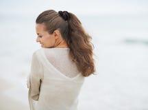 Портрет молодой женщины в свитере на сиротливом пляже Стоковое Фото