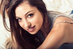Портрет молодой женщины в спальне на кровати самостоятельно ослабляя Стоковая Фотография