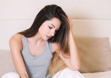 Портрет молодой женщины в спальне на кровати самостоятельно ослабляя Стоковые Изображения