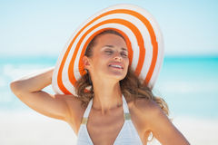 Портрет молодой женщины в шляпе загорая на пляже стоковые изображения
