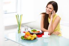 Портрет молодой женщины говоря на мобильном телефоне дома Стоковые Изображения RF