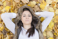 Портрет молодой женщины лежа на листьях осени Стоковое Фото