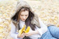 Портрет молодой женщины лежа на листьях осени Стоковые Изображения RF
