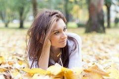 Портрет молодой женщины лежа на листьях осени Стоковые Фото