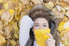 Портрет молодой женщины лежа на листьях осени Стоковые Изображения