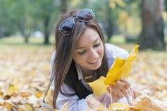 Портрет молодой женщины лежа на листьях осени Стоковое Изображение RF