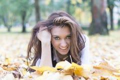 Портрет молодой женщины лежа на листьях осени Стоковая Фотография RF