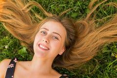Портрет молодой женщины лежа на траве Стоковое Изображение