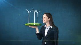 Портрет молодой женщины держа ветрянку на открытой ладони руки, над изолированной предпосылкой студии Дело, концепция eco Стоковые Изображения RF