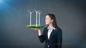 Портрет молодой женщины держа ветрянку на открытой ладони руки, над изолированной предпосылкой студии Дело, концепция eco Стоковая Фотография