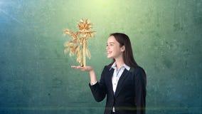 Портрет молодой женщины держа золотую ладонь на открытой ладони руки, над изолированной предпосылкой студии владение домашнего кл Стоковое Изображение