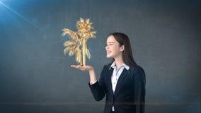 Портрет молодой женщины держа золотую ладонь на открытой ладони руки, над изолированной предпосылкой студии владение домашнего кл Стоковые Изображения RF