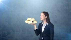 Портрет молодой женщины держа золотые бары на открытой ладони руки, над изолированной предпосылкой студии владение домашнего ключ Стоковая Фотография RF
