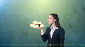 Портрет молодой женщины держа золотые бары на открытой ладони руки, над изолированной предпосылкой студии владение домашнего ключ Стоковое Изображение RF