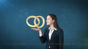 Портрет молодой женщины держа золотые обручальные кольца на открытой ладони руки, изолированную предпосылку студии владение домаш Стоковые Фотографии RF