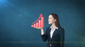 Портрет молодой женщины держа растущую диаграмму 3D на открытой ладони руки, над изолированной предпосылкой студии владение домаш Стоковые Изображения RF