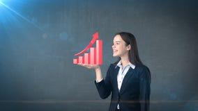 Портрет молодой женщины держа растущую диаграмму 3D на открытой ладони руки, над изолированной предпосылкой студии владение домаш Стоковые Фото
