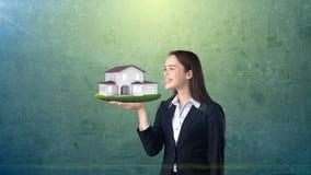 Портрет молодой женщины держа современный дом на открытой ладони руки, над изолированной предпосылкой студии владение домашнего к Стоковая Фотография