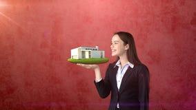 Портрет молодой женщины держа современный дом на открытой ладони руки, над изолированной предпосылкой студии владение домашнего к Стоковое фото RF