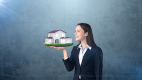 Портрет молодой женщины держа современный дом на открытой ладони руки, над изолированной предпосылкой студии владение домашнего к Стоковая Фотография RF