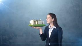 Портрет молодой женщины держа современный дом на открытой ладони руки, над изолированной предпосылкой студии владение домашнего к Стоковое Изображение