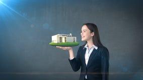 Портрет молодой женщины держа современный дом на открытой ладони руки, над изолированной предпосылкой студии владение домашнего к Стоковое Изображение RF