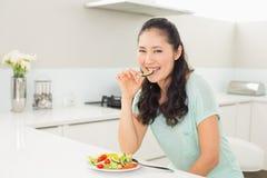 Портрет молодой женщины есть салат в кухне Стоковое Изображение
